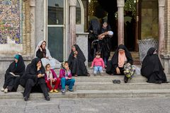 Iranian women and children sit near the mosque, Tehran, Iran. Tehran, Iran - April 27, 2017: Iranian women in hijabs and children sit on the steps near the Shah Stock Photography
