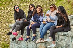 Iranian women laugh and drink cocktails in park, Tehran, Iran. Tehran, Iran - April 28, 2017: Iranian women with cocktails in their hands are sitting in the Stock Photo