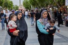 Iranian women walk down the street, Tehran, Iran. Tehran, Iran - April 27, 2017: two Iranian women in hijabs with children in their arms are walking along the stock photos