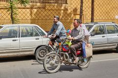Iranians on a motorcycle on busy street, Kashan, Iran. Kashan, Iran - April 27, 2017: Iranian man and his children are riding a motorcycles down the street Royalty Free Stock Images