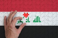 Iraq flag is depicted on a puzzle, which the man`s hand completes to fold.  vector illustration