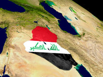 Iraq with flag on Earth Stock Images