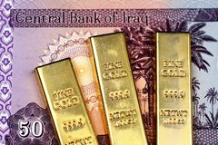 An Iraqi fifty dinar note with three golden ingots. Close up image of an Iraqi 50 dinar bank note with three golden ingots royalty free stock photos