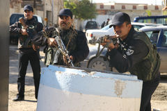 Iraqi Policemen in Kirkuk. Iraqi Policemen overwatche random searches of vehicles with machine guns at a checkpoint along a road of Kirkuk Stock Photography