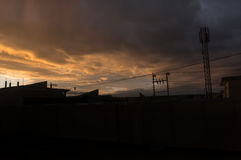 Iraqi Sunset Skyline. Iraqi Houses in sunset with electrical grid and clouds. There is a cellphone tower at the background Stock Photo