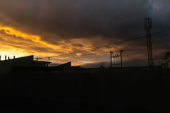 Iraqi Sunset Skyline. Iraqi Houses in sunset with electrical grid and clouds. There is a cellphone tower at the background Stock Images
