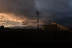 Iraqi Sunset Skyline. Iraqi Houses in sunset with electrical grid and clouds. There is a cellphone tower at the background Stock Photography
