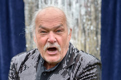 Irate balding man yelling at the camera. Irate grey haired balding man glaring and yelling at the camera with a fierce expression in a head and shoulders view stock photos