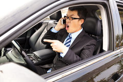 Irate businessman talking with cell phone Stock Image