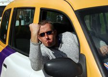 Irate cab driver. Angry taxi driver waving his fist at the traffic Royalty Free Stock Photo