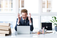 Irate employee laboring with loathing. Detest my job. Portrait of young angry businessman is working on laptop in office. Screaming man is expressing hate and Royalty Free Stock Photo