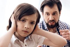 Irate father scolds teenage son which plugs ears. stock photo