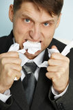 Irate manager tears teeth documents Stock Photography