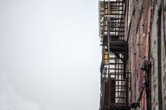 Ire vlucht roestige treden en ladder, in metaal, op een typisch Noordamerikaans oud baksteengebouw van Montreal, Quebec, Canada royalty-vrije stock foto's