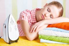 Ired housewife fell asleep on ironing board with iron Stock Photography
