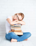 Ired student girl asleep hugging books stock image