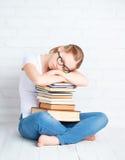 Ired student girl asleep hugging books Stock Image