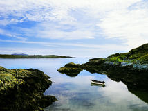 Ireland. A fishing boat moored on a still sea in a cove, schull bay, mizen peninsula, countty cork, west coast of ireland, europe eu Royalty Free Stock Photography