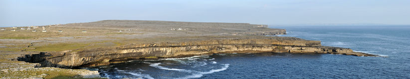 Ireland Aran island cliffs and stone wall panorama. A lacework of ancient stone walls (1,600 km or 1,000 mi in all) enfolds all three islands to contain local Royalty Free Stock Photo