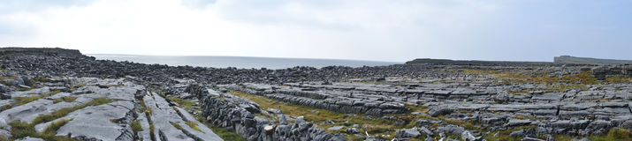 Ireland Aran island rocks panorama. And Dun Aonghasa (anglicized Dun Aengus) prehistoric fortress at the background Royalty Free Stock Photo
