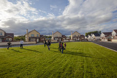 Ireland Children Football Homes. Local young children play football soccer on the large green field between their homes at days end in the north west Leitrim Royalty Free Stock Image