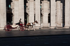 Ireland. Dublin. Turistic buggy pulled by horse passes on OConnell Street in front of the historic building of the General Post Office (GPO). An original way to Stock Images
