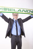 Ireland fan. Young man holding Ireland flag cheering Royalty Free Stock Images
