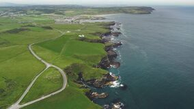 Ireland farmland, ocean bay aerial view: rocky shore of Antrim County. Epic Irish landmark landscape