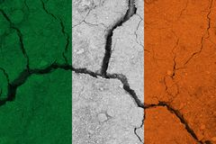 Ireland flag on the cracked earth. National flag of Ireland. Earthquake or drought concept royalty free stock photography
