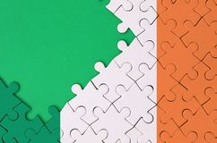 Ireland flag is depicted on a completed jigsaw puzzle with free green copy space on the left side.  stock images