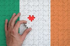 Ireland flag is depicted on a puzzle, which the man`s hand completes to fold.  stock image