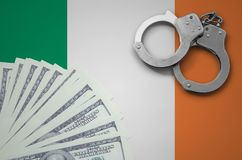 Ireland flag with handcuffs and a bundle of dollars. The concept of illegal banking operations in US currency.  royalty free stock photography
