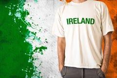 Ireland flag. Man in white shirt with title IRELAND, irish flag in background Royalty Free Stock Image