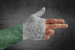 Ireland flag painted on male hand like a gun. Isolated on concrete stock photos
