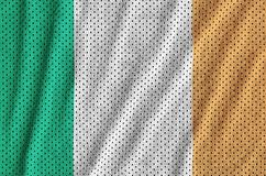 Ireland flag printed on a polyester nylon sportswear mesh fabric. With some folds stock photos