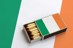 Ireland flag is shown in an open matchbox, which is filled with matches and lies on a large flag.  royalty free stock photo