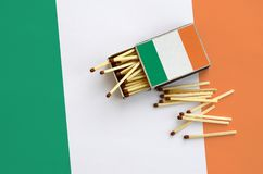 Ireland flag is shown on an open matchbox, from which several matches fall and lies on a large flag.  stock photo