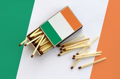 Ireland flag is shown on an open matchbox, from which several matches fall and lies on a large flag.  stock images