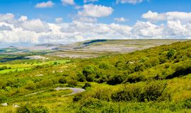 Ireland Landscape. Landscape of County Clare, Ireland. Green fields, trees, and a winding road in foreground and The Burren and sky in the background Royalty Free Stock Images