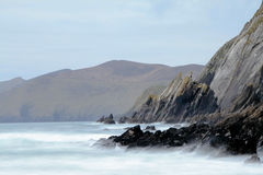 Ireland seashore at Dingle peninsula. Beat of waves at rocky beach in Dingle peninsula during windy sunset Stock Photo