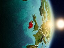 Ireland during sunrise. Highlighted in red on planet Earth with visible country borders. 3D illustration. Elements of this image furnished by NASA Royalty Free Stock Photo
