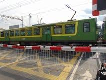 Irelands DART Train Passing Barrier Stock Image