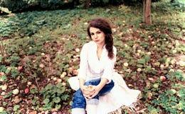 Irgendwelche stauen (das Mädchen, das im Garten auf dem Gras sitzt) stockbilder