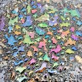 Iridescent overflows of petrol spots on the surface of the water on the asphalt. Stock Photography
