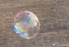 Iridiscente grande de la burbuja de jabón con un primer iridiscente del modelo contra un fondo de la piedra Imágenes de archivo libres de regalías