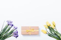 Iris púrpuras, tulipanes amarillos y caja de regalo con el arco en la parte posterior del blanco Foto de archivo libre de regalías