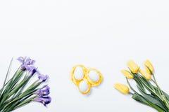 Iris púrpuras, tulipanes amarillos y jerarquía con los huevos de Pascua en blanco Fotografía de archivo