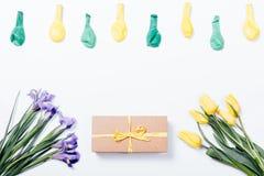 Iris pourpres, tulipes jaunes, boîte-cadeau avec l'arc et ballons dessus Image stock