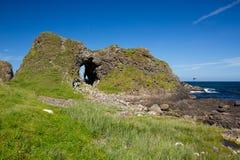 Irische Landschaft, grünes Gras bedeckte Seeküste, mit Steinhügel und Höhle, nahe bei Ballintoy Lizenzfreie Stockfotografie