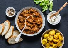 Irische Rindereintopf- und Gelbwurzkartoffeln - köstliches Saisonmittagessen auf einem dunklen Hintergrund, Draufsicht Flache Lag Lizenzfreies Stockbild